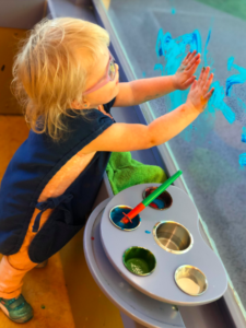 A young child is standing and hand painting on the wall with both hands.